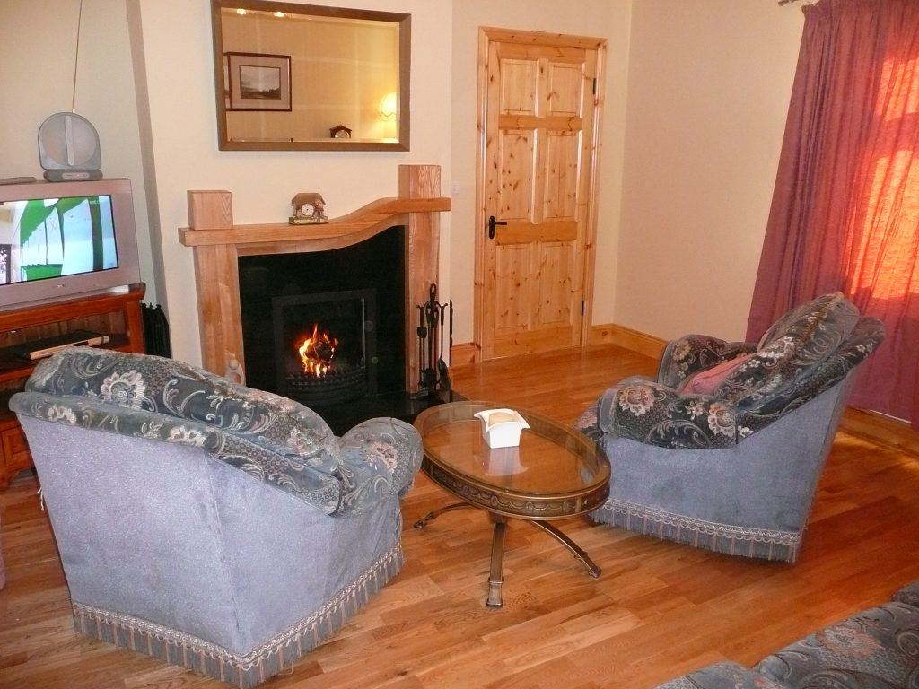 Skelligs House, Living Room with Couch, Cairs and a cosy Fire. Rent an Irish Cottage with Sea View along the Wild Atlantic Way in Kerry from www.fir-darrig.net. Rent a Holiday Home with Seaview in Ireland along the Ring of Kerry.