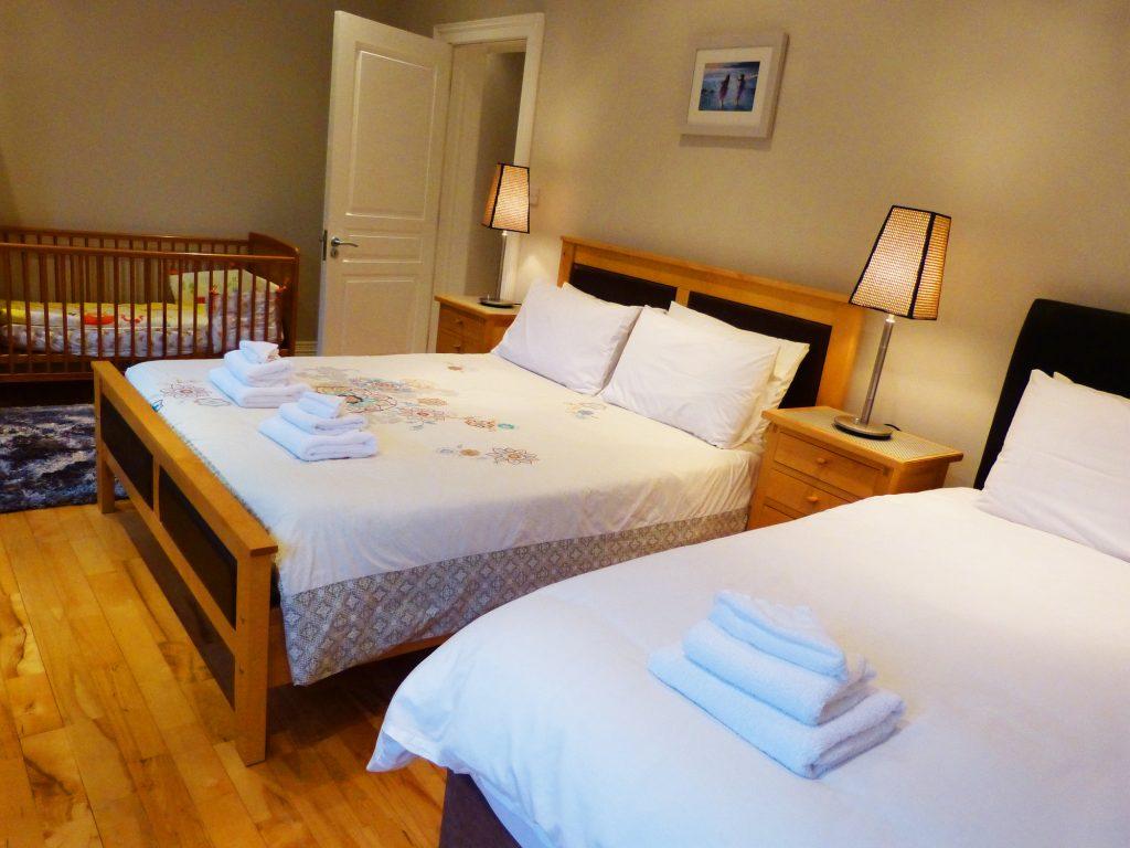 Schlafzimmer 1 EG ein Doppelbett ein Einzelbett ein Babybett, Toilette Waschbecken von Ferienhaus Castle View in Glenbeigh in Kerry, Irland.