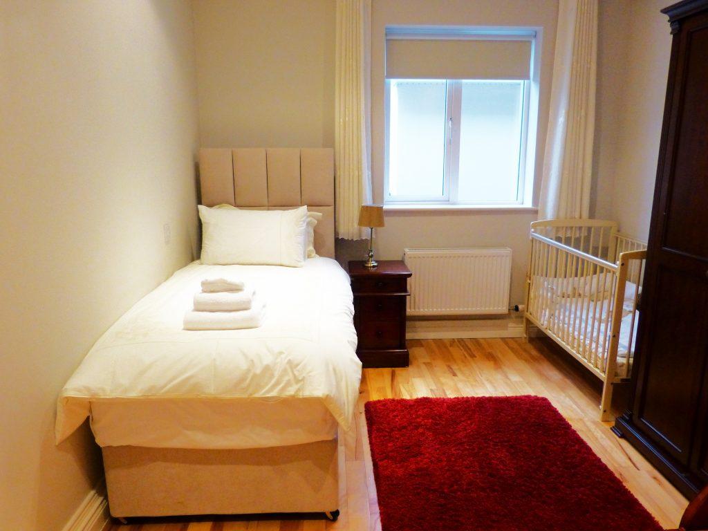 Ein Einzelbett und ein Babybett in Schlafzimmer zwei im Erdgeschoss von Ferienhaus Castle View in Glenbeigh in Kerry, Irland.