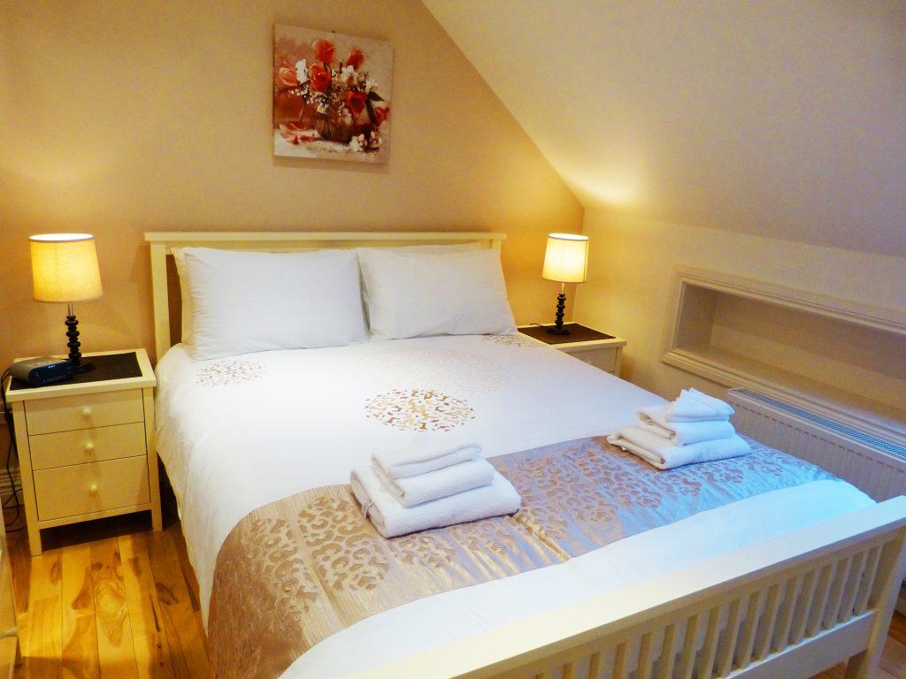Zwei Doppelbetten und Bad zum Schlafzimmer drei auf der ersten Etage von Ferienhaus Castle View in Glenbeigh in Kerry, Irland.