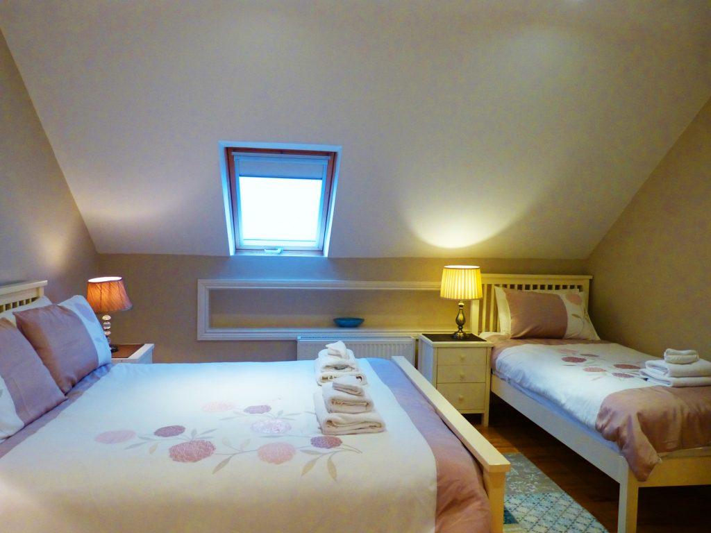Ein Doppelbett und ein Einzelbett im Schlafzimmer fünf auf der ersten Etage von Ferienhaus Castle View in Glenbeigh in Kerry, Irland.