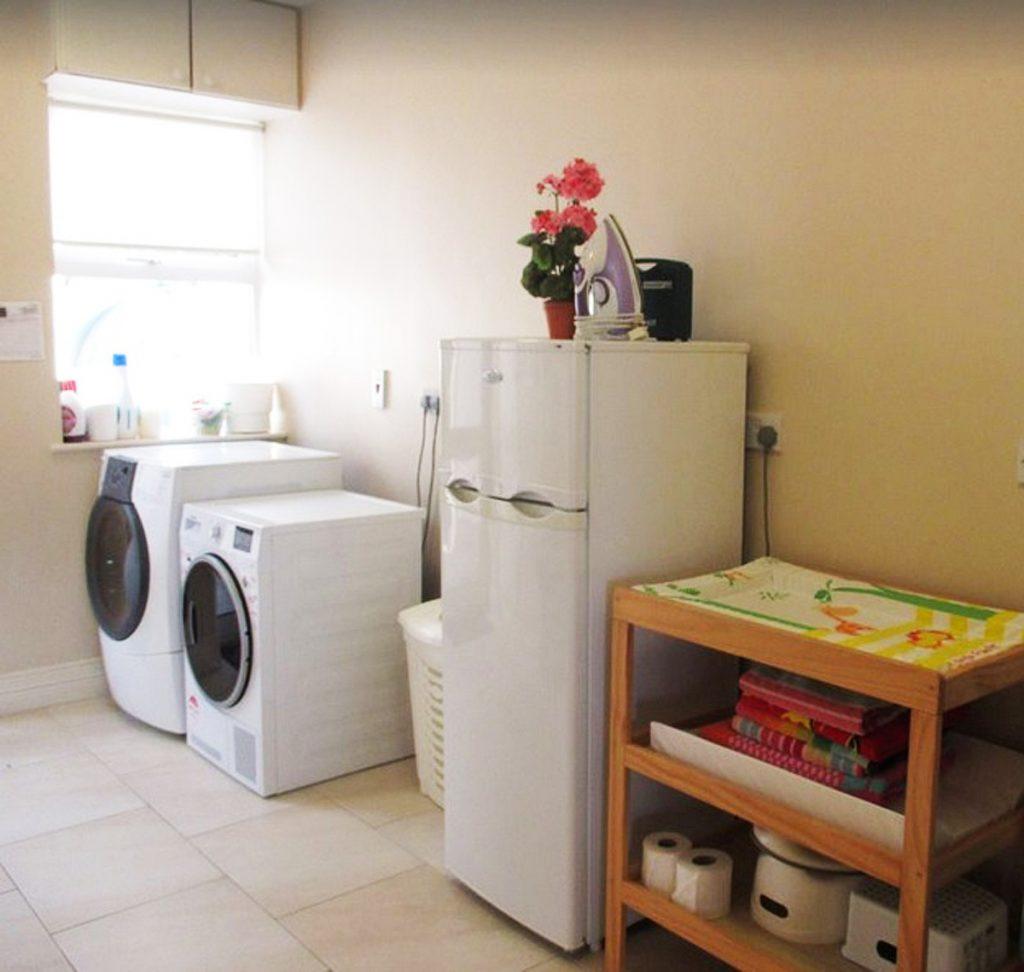 Der Hauswirtschaftsraum mit Waschmaschine, Trockner und Extra-Kühlschrank im Ferienhaus Castle View in Glenbeigh in Kerry, Irland.