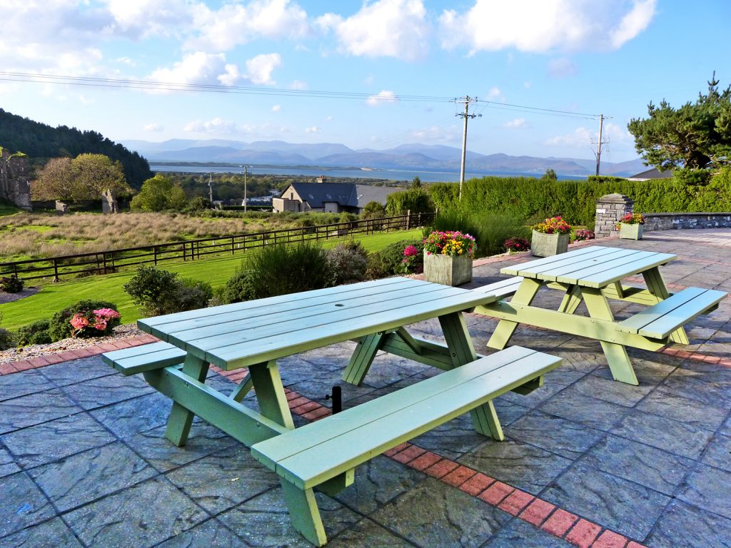 Patio with two Picnic Tables at Holiday Home Castle View in Glenbeigh, County Kerry, Irland.